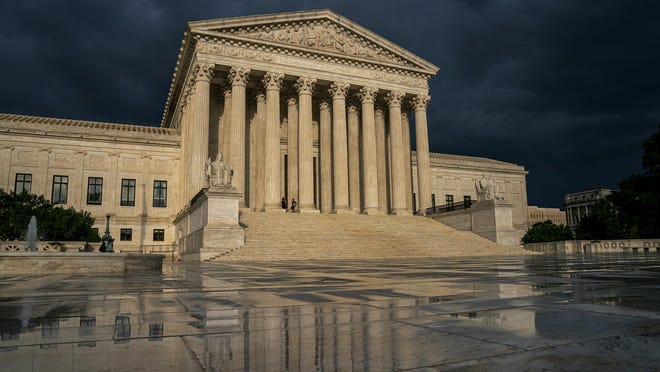 FILE - In this June 20, 2019 file photo, the Supreme Court is seen under stormy skies in Washington. Two issues that could determine the distribution of political power for the next decade await resolution on the Supreme Court's final day of decisions before a long summer break. Chief Justice John Roberts could well be the author of decisions on both politically charged topics Thursday, June 27, whether to allow a citizenship question on the 2020 census and place limits on drawing electoral districts for partisan gain. (AP Photo/J. Scott Applewhite, File)