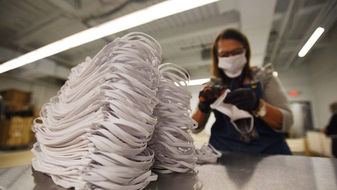 A pile of masks is seen as a worker continues to make masks at Laundry Bags Unlimited in Paterson, NJ, on March 25. Laundry Bags Unlimited switched from manufacturing backpacks and cosmetic supply cases to churning out 100,000 protective masks a week, with plans to double that capacity.