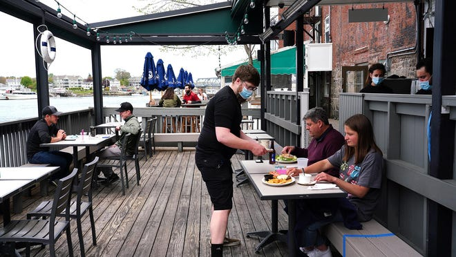 Servers wear face masks while attending to customers on the outdoor decks at River House in Portsmouth which opened for outdoor dining earlier this month.