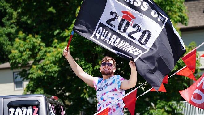 Winnacunnet High School senior Michael Dunleavy of Hampton waves a Class of 2020 Quarantined flag in a parade through Hampton.