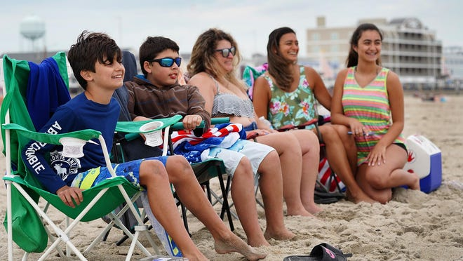 Matthew Fasulo, 10, his buddy Rauh Brandao, 10, Sandra Goncalves, Anna Fasulo and her daughter Ashley, 14, of Hudson, Massachusetts, enjoy their first day back on the sand at Hampton Beach Friday, where sunbathers are now allowed again.
