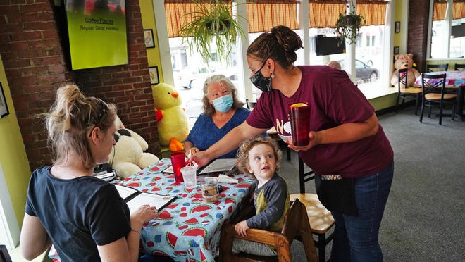 Server Krystal Webber brings drinks to Dorothy Matthews and her son Edward, 2, of Kennebunk, and Dorothy's mother Mary Sindut of Durham Monday at The Nook in Dover. Gov. Chris Sununu lifted the state's stay-at-home order Monday, and Seacoast area restaurants could reopen indoors at 50% seating capacity.
