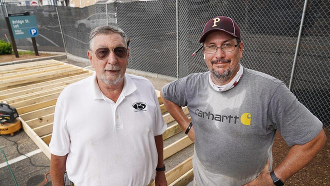 Rick Becksted Sr., left, and his son, Mayor Rick Becksted, pause while building the stage for a pop-up food and entertainment venue on the Bridge Street parking lot.