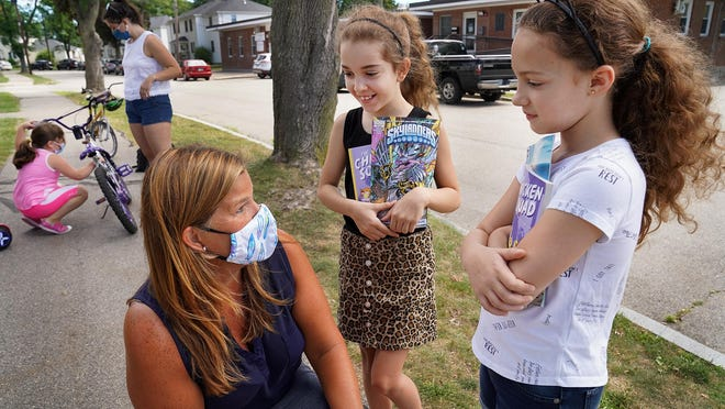 Donna Turco, reading specialist at New Franklin School, visits with Andrea Hatch, 8, center, and her sister, Aleeyah Kimber, 8, after book distributions to the Gosling Meadows neighborhood in Portsmouth Monday.