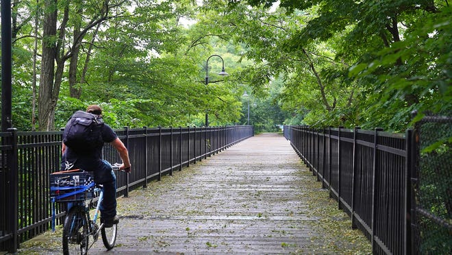 A bicyclist rides over the wooden bridge on the Dover Community Trail.