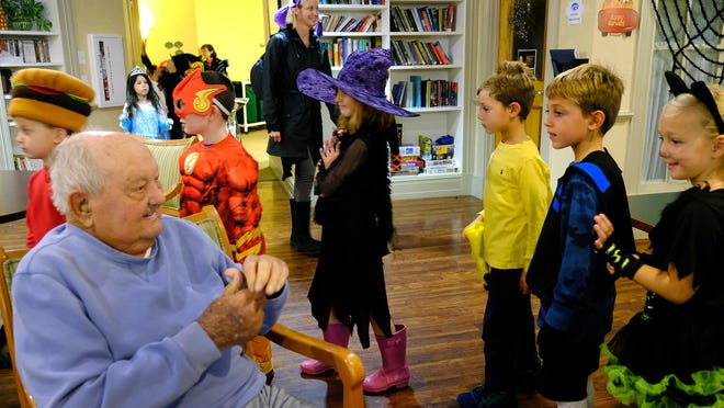 In 2019, resident John Welch smiles at first-graders from Village Elementary School in York, Maine, as they wear their costumes for a Halloween parade through Sentry Hill in York in 2019.