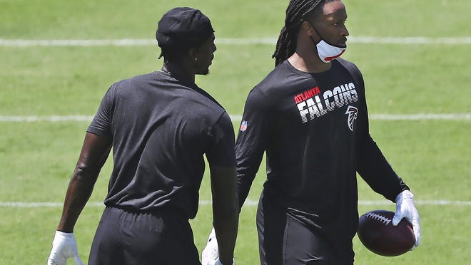 FILE - In this Aug. 4, 2020, file photo, Atlanta Falcons running back Todd Gurley, right, gets five from wide receiver Calvin Ridley after making a reception during NFL football practice in Flowery Branch, Ga. Gurley believes he and his new team are a perfect match as he seeks to rejuvenate a career affected by knee injuries.