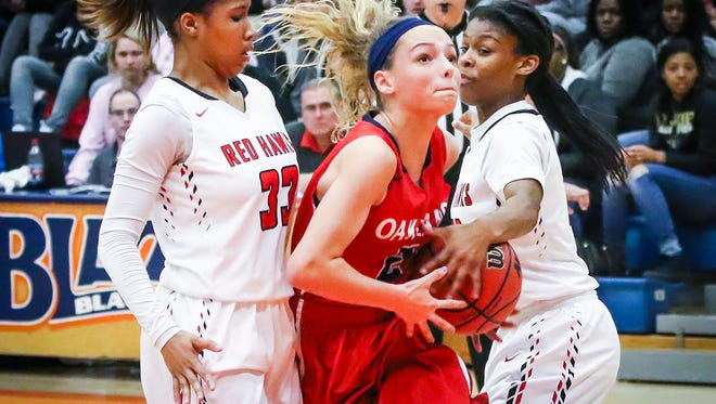 Oakland's Faith Adams drives between Stewarts Creek's Brandi Ferby (left) and Lauren Flowers Saturday.