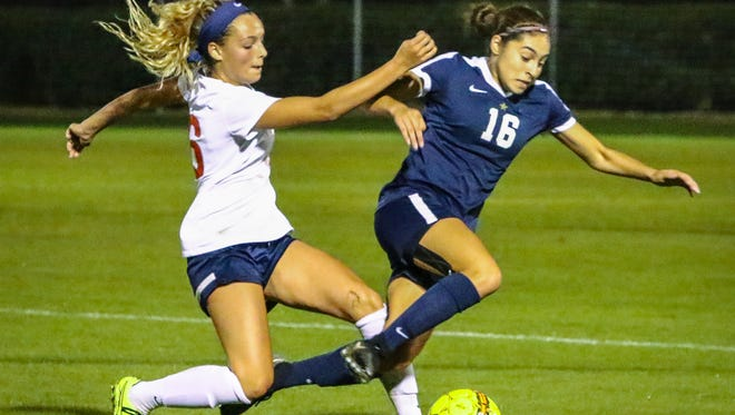 Oakland's Faith Adams (left) and Siegel's Emily Sanchez battle downfield during Thursday's 7-AAA title match. Both players scored in Siegel's 2-1 win, with Sanchez netting the game-winner in overtime.
