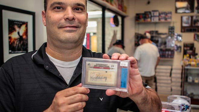 Nathan Burns, owner of opened Grand Slam Collectibles in Murfreesboro, holds a cut signature from Major League Baseball Hall of Famer Ty Cobb.