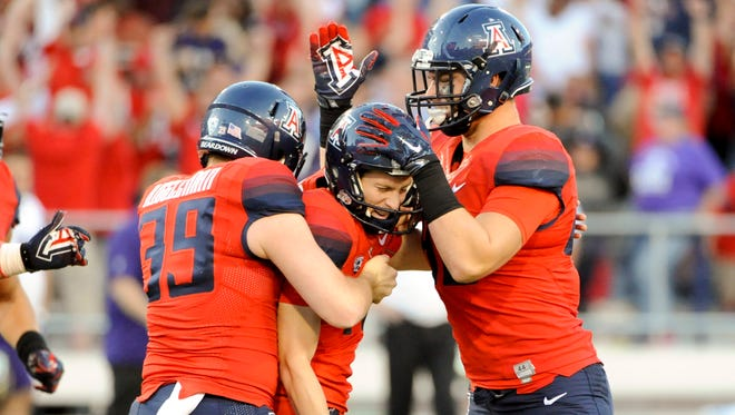 Arizona Wildcats place kicker Casey Skowron (41) is congratulated by punter Drew Riggleman (39) and tight end Trevor Wood (88) after kicking the winning field goal against the Washington Huskies at Arizona Stadium.