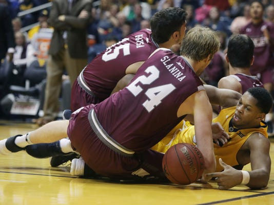 West Virginia forward Sagaba Konate (50) wrestles for control of a loose ball during the first half of an NCAA college basketball game against Fordham Saturday, Dec. 23, 2017, in Morgantown, W.Va. (AP Photo/Raymond Thompson)