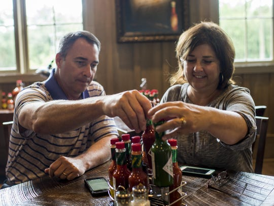Cecil Hymel, vice president of administration for the McIlhenny Company, and Angie Schaubert, the company's senior manager of brand sales, sort through a selection of the company's Tabasco sauce line in their new restaurant 1868 on Avery Island, Tuesday, Aug. 4, 2015.