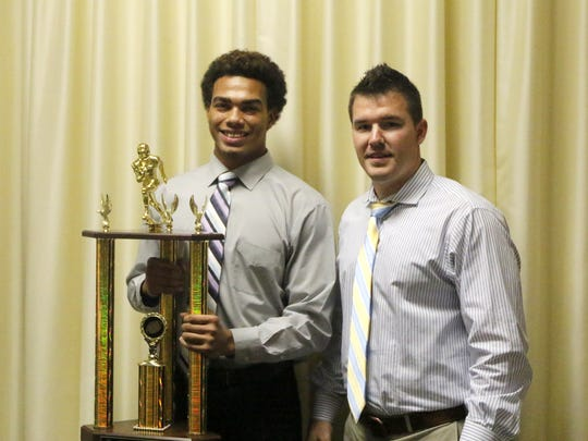 Elmira's Allaah Sessions is accompanied by Express head coach Jimmy McCauley as he holds the Ernie Davis Award on Thursday.