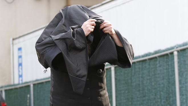Peretz Klein, owner of Hashomer Alarm, Inc. is seen leaving his office at 29 Robert Pitt Drive in Spring Valley, cloaked under his jacket as federal agents collect evidence on Wednesday, March 16, 2016.