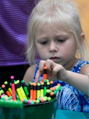 Dollie Shaw, 4, picks out a pencil at the Back to School