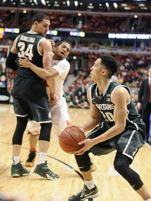 MSU's Gavin Schilling, behind, sets an effective pick on Maryland's Jared Nickens to free up Travis Trice for a successful 3-point shot during their Big Ten Tournament game in Saturday in Chicago.