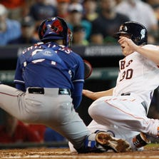 HOUSTON, TX - AUGUST 10:  Matt Dominguez #30 of the Houston Astros is tagged out at home by Robinson Chirinos #61 of the Texas Rangers attempting to score in the second inning at Minute Maid Park on August 10, 2014 in Houston, Texas. Umpire reviewed (home-plate collision), and the call on the field was upheld. (Photo by Bob Levey/Getty Images)
