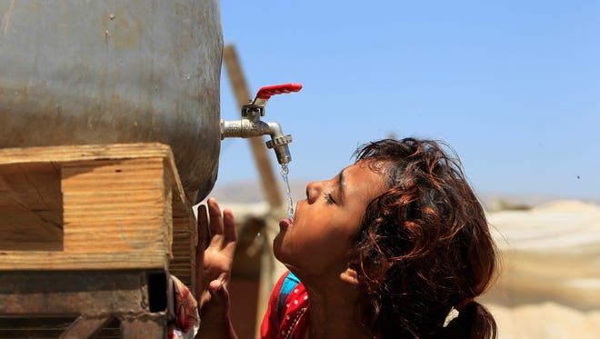 Syrian refugee Amani al-Antar, 7, who fled with her family from the city of Deir al-Zour, Syria, drinks water at a Syrian refugee camp in the eastern Lebanese town of Saadnayel, Bekaa Valley, Lebanon.