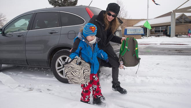 Julie Prophet walks with her son, Keegan, as she drops him off at Linton Elementary School on Thursday, December 21, 2017.