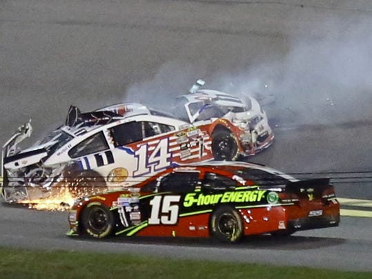 Clint Bowyer (15) runs into Brian Vickers (14) after Vickers wrecked coming out of turn 1 during the Sprint Unlimited auto race at Daytona International Speedway, Saturday, Feb. 13, 2016, in Daytona Beach, Fla. (AP Photo/David Graham)