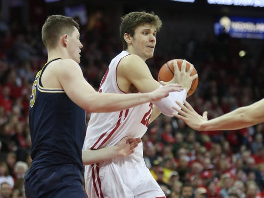 Wisconsin Badgers forward Ethan Happ  looks to pass as Michigan Wolverines center Jon Teske (left) defends at the Kohl Center Feb. 11, 2018.