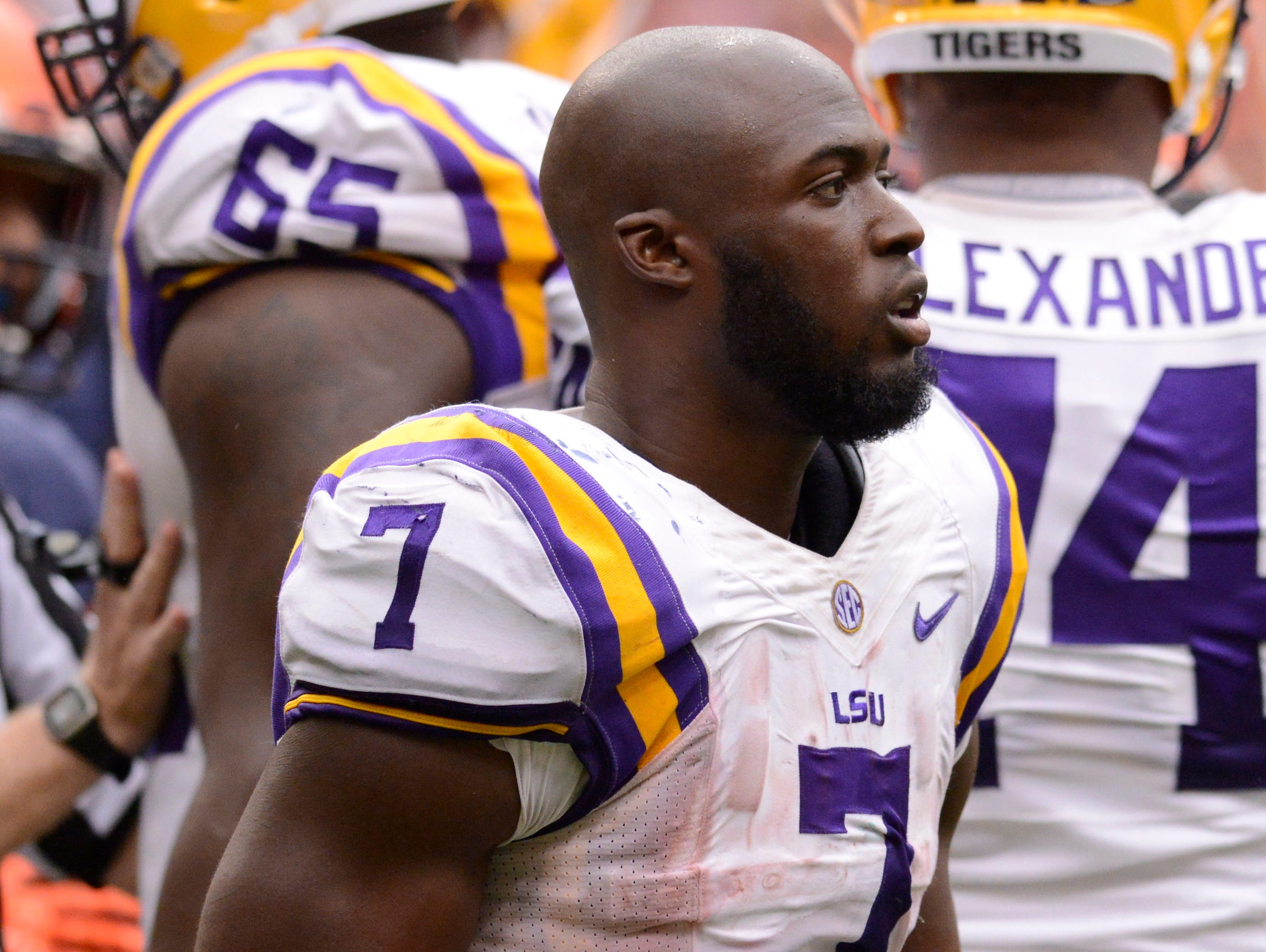 LSU Tigers running back Leonard Fournette (7) gathers his helmet after losing it on a play in the fourth quarter of a game against the Syracuse Orange at the Carrier Dome. LSU won the game 34-24.
