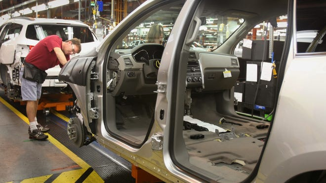 A GM employee installs lights on the assembly line for the Chevy Traverse at the GM plant in Spring Hill.