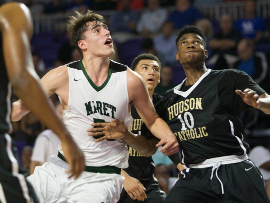 Maret High School's Luke Garza, left, looks to rebound against Hudson Cathloic's Precious Ikediaschi during play Friday (12/16/16) at the Culligan City of Palms Classic at the Suncoast Credit Union Arena in Fort Myers. Hudson beat Maret 65-51.