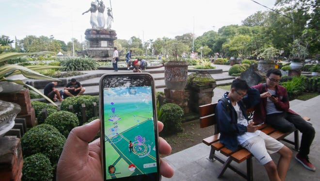A person plays with Pokemon Go on his mobile phone at a park in Denpasar, Bali, Indonesia, a Muslim majority country. Saudi Arabia clerics have issued a fatwa banning the game as a form of gambling.