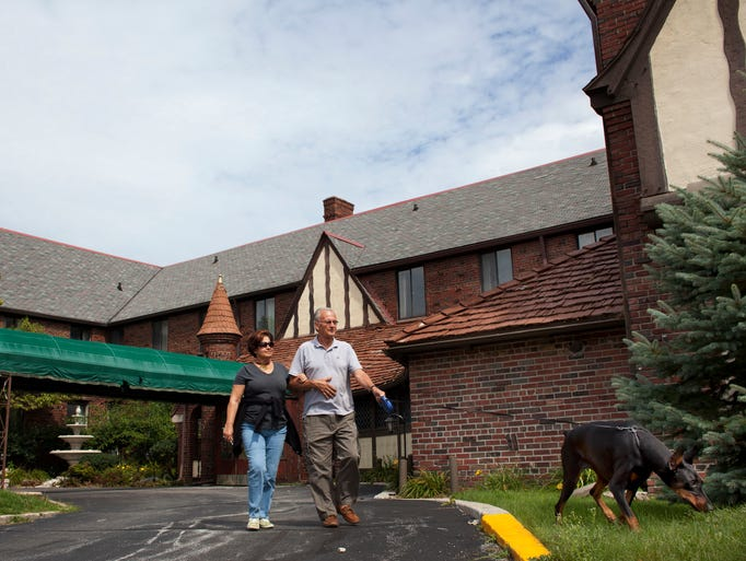 "Florida resident and St. Clair Native Joe Garrick walks with his wife, Lauren Garrick, and dog, KC, August 29, 2014 in front of the St. Clair Inn, 500 Riverside Ave., in downtown St. Clair. ""My uncle did a lot of the brick laying,"" Joe Garrick said, while recalling memories of the historic hotel."
