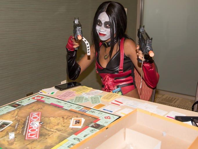 Shadava Esquioin as Harley Quinn, plays Monopoly during
