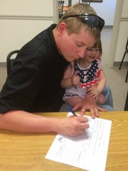 John Bouligny, treasurer of San Angelo Police Officers Association, with his daughter Christy on his lap, signs the petition to recall Richardson.