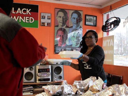 Alyssa Williams, right, of Brothers & Sisters Unisex Salon serves a Thanksgiving meal to a customer Thursday.