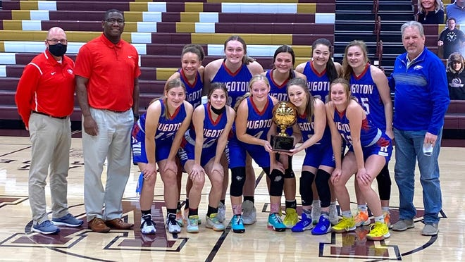 The Hugoton High School girls' basketball team celebrates winning the Hays Shootout Saturday at Hays.