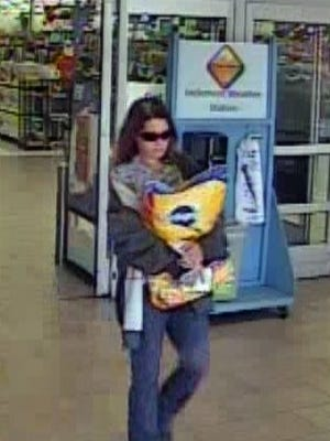 Surveillance images of woman accused of using stolen credit card at Titusville stores.