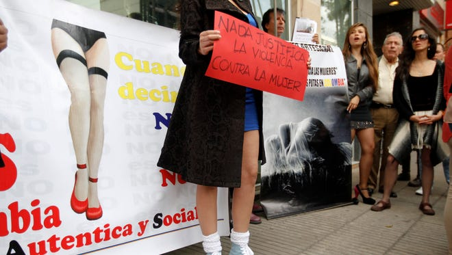 "A woman holds a sign reading in Spanish ""Nothing justifies violence against women"" in front of Andres D.C. restaurant in Bogota, Colombia on Sunday."
