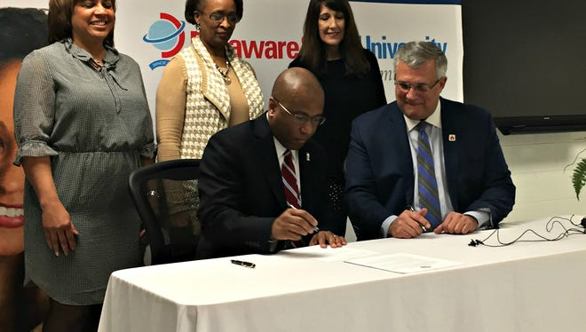 Delaware State University President Harry Lee Williams (left) and Red Clay Superintendent Marvin Daugherty sign an agreement allowing Red Clay students to take technology classes at a new IT Center at DSU's Wilmington campus.