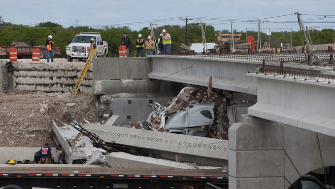 Authorities investigate a tractor-trailer that crashed into an overpass under construction March 26, 2015, in Salado, Texas.