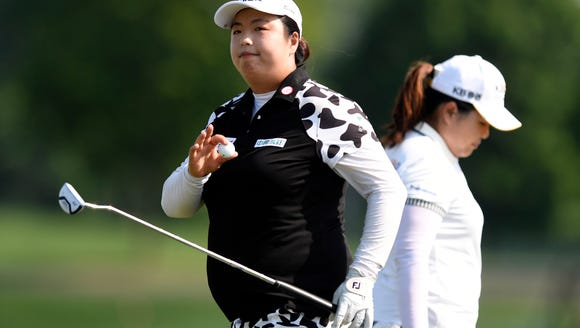 Shanshan Feng, left, waves to the crowd after sinking