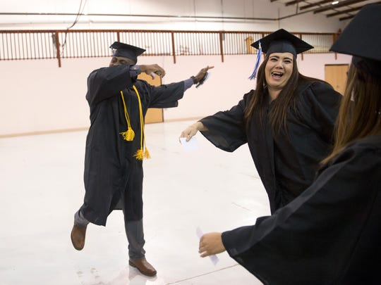 Sudul Diahkah, left, dances with his classmates before the start of the Charter Institute's commencement ceremony Friday at the McGee Park Convention Center.