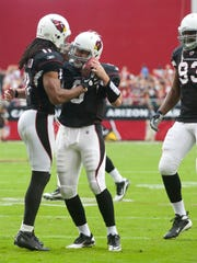 Cardinals wide receiver Larry Fitzgerald gives the ball he just scored a touchdown with to quarterback Max Hall during the first half of the NFL game against the Buccaneers at University of Phoenix Stadium in Glendale on Sunday, October 31, 2010. This was Hall's first NFL touchdown pass.