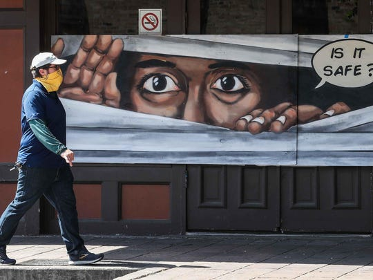 A man walks in front of a mural on Sixth Street wearing a face mask in late April. A study published by a Texas A&M professor suggests that such masks are significantly more effective in stopping the spread of the coronavirus than other measures.