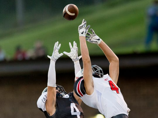 Anderson County's Dalton Wilson (4) and Heritage's Tim Shultz (4) reach for a ball but either does not catch it during a game between Anderson County and Heritage at Anderson County High School in Clinton, Tennessee on Friday, September 22, 2017.