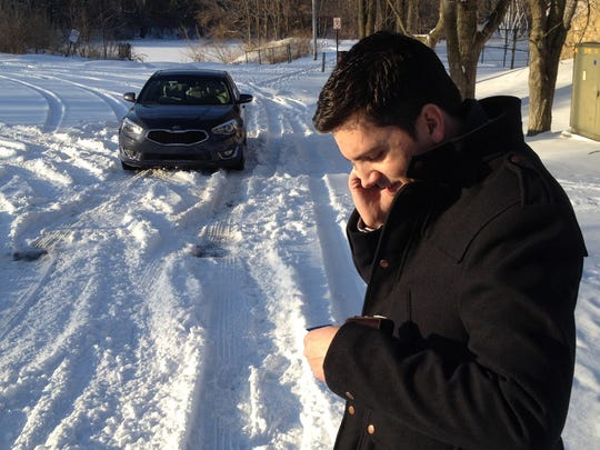 Casey Williams takes a moment to call in help from a tow truck after deciding the 2014 Kia Cadenza would handle this patch of road better with snow tires.