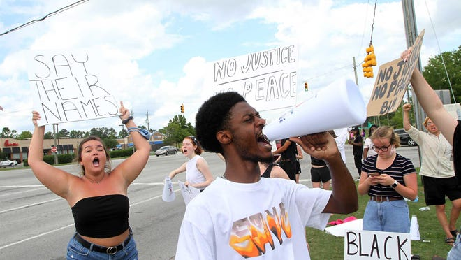 Demonstrators gather along the 3100-block of Doctor M.L.K. Jr Blvd. in New Bern N.C., May 30 2020. The vocal group carrying signs and banners are protesting the recent death of Minneapolis, Minn. resident George Floyd and racial injustices across the nation. Floyd's reported death, which occurred on May 25, 2020, after a Minneapolis police officer knelt on Floyd's neck for more than 8 minutes. The officer has been charged with third-degree murder and second-degree manslaughter. Protests have been occurring nationally since Floyd's death.