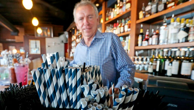 Duke Moscrip, owner of Duke's Restaurants, bar at his restaurant in Seattle with the paper straws his eateries will now use. Businesses that sell food or drinks won't be allowed to offer the plastic items under a rule that went into effect Sunday.