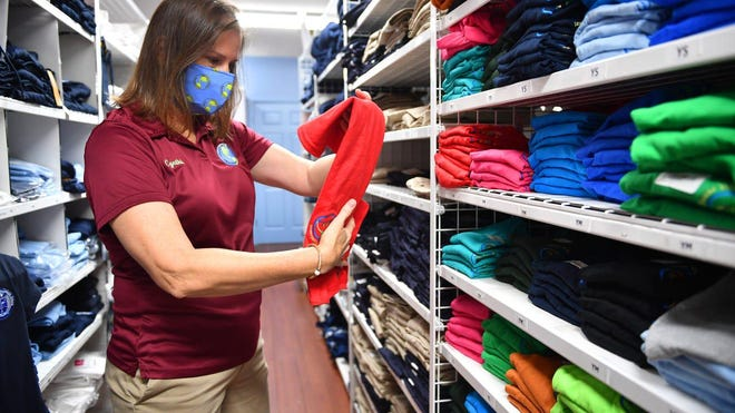 Cynthia Holliday, co-owner of Children's World Uniform Supply on Bee Ridge Road, folds shirts Thursday in hopes of a busy weekend. Florida's 2020 back-to-school sales tax holiday runs Friday through Sunday.