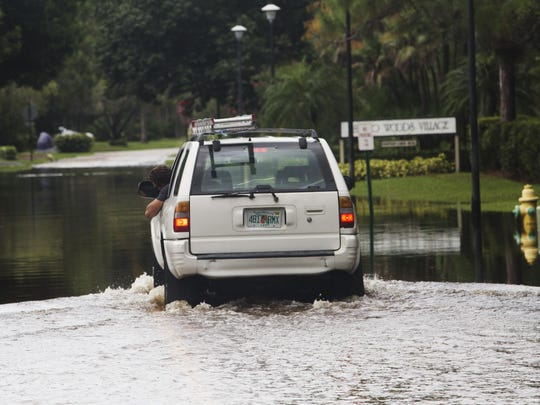 A driver braves a flooded street in the Fountain Lakes community in Estero on Monday. Heavy rains have been flooding area streets.