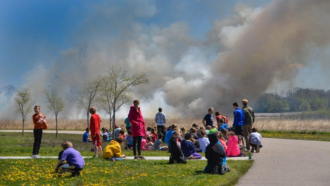 Kennedy Community School students watch the prairie burn from a safe distance Wednesday, May 4, in St. Joseph.